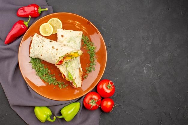 Bovenaanzicht heerlijke gesneden shaurma sandwich met verse groenten op de donkere achtergrond hamburger maaltijd sandwich snack brood