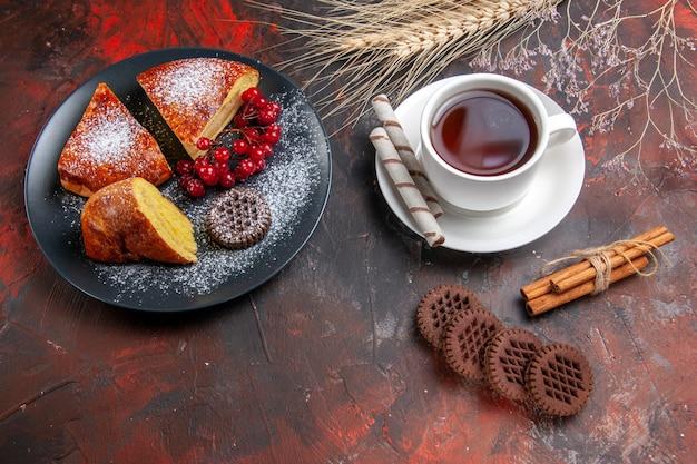 Bovenaanzicht heerlijke gesneden taart met koekjes en kopje thee op donkere tafel zoete taartcake