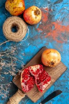 Bovenaanzicht heerlijke granaatappels op snijplank diner mes stro draad op blauwe achtergrond
