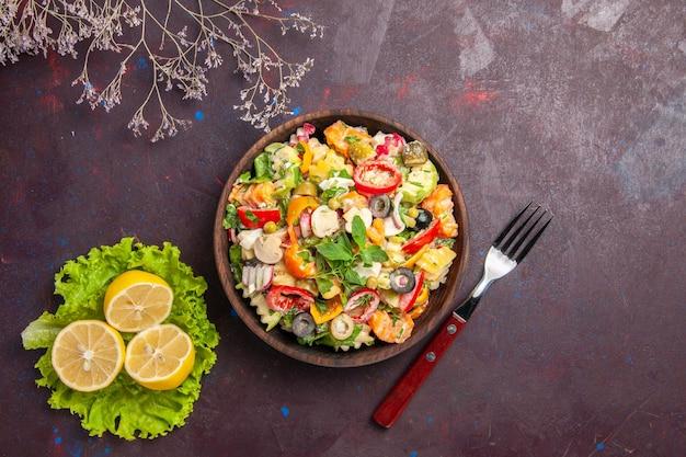 Bovenaanzicht heerlijke groentesalade met schijfjes citroen en groene salade op een donkere achtergrond salade maaltijd gezondheidsdieet