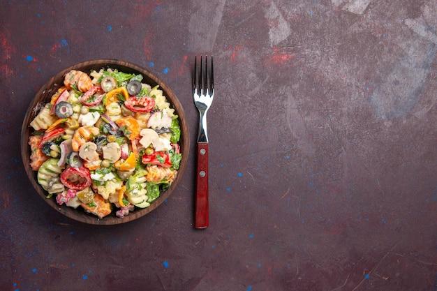 Bovenaanzicht heerlijke groentesalade met tomaten, olijven en champignons op de donkere achtergrond gezondheidsdieet salade groente lunch snack