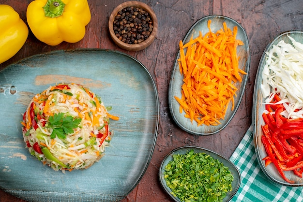 Bovenaanzicht heerlijke groentesalade met vers gesneden groenten op een donkere achtergrondkleur rijp voedsel maaltijd gezond leven foto