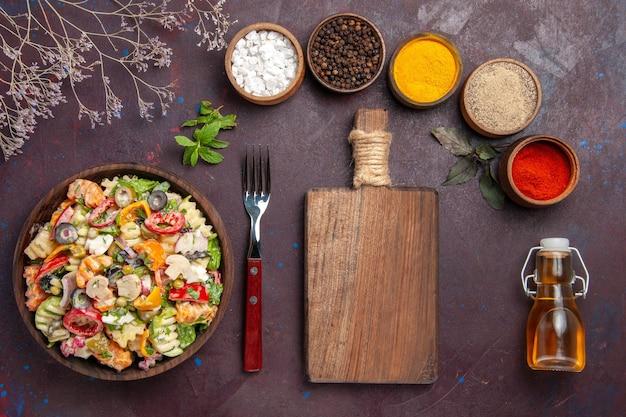 Bovenaanzicht heerlijke groentesalade met verschillende smaakmakers op een donkere achtergrond gezonde groentesalade dieet lunch