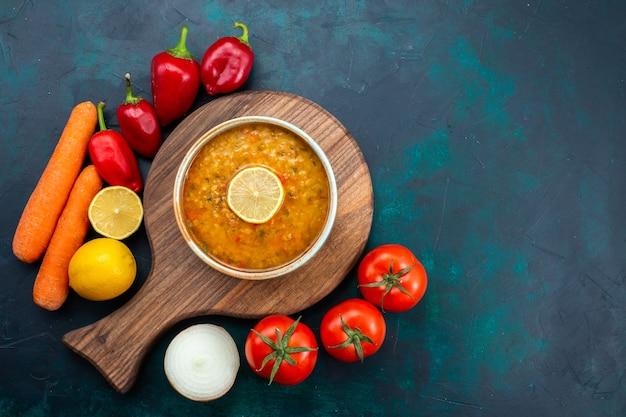 Bovenaanzicht heerlijke groentesoep binnen ronde plaat met citroen en verse groenten op het donkerblauwe bureau.