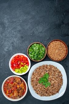 Bovenaanzicht heerlijke groentesoep met gekookte boekweit op grijze ruimte