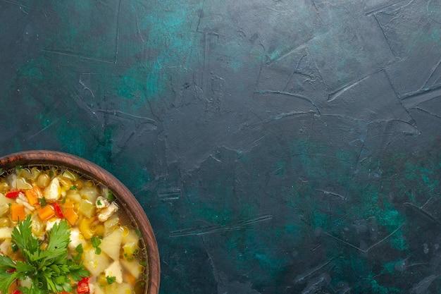 Bovenaanzicht heerlijke groentesoep met gesneden groenten en greens op de donkerblauwe achtergrond soep groente eten maaltijd warm eten diner saus