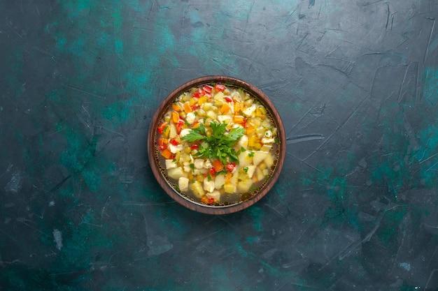 Bovenaanzicht heerlijke groentesoep met gesneden groenten en greens op donkerblauwe achtergrond soep groenten eten maaltijd warm eten diner saus