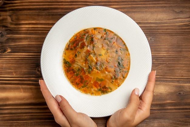 Bovenaanzicht heerlijke groentesoep met greens op bruine houten tafel soep eten groentekruiden