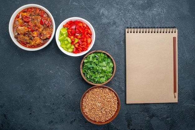 Bovenaanzicht heerlijke groentesoep met greens op grijze ruimte