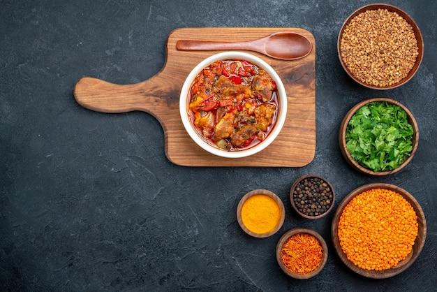 Bovenaanzicht heerlijke groentesoep met kruiden en groenten op donkere ruimte
