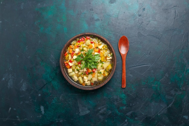 Bovenaanzicht heerlijke groentesoep met verschillende ingrediënten in bruine plaat op het donkere bureau soep groenten saus maaltijd eten warm eten schotel