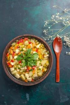 Bovenaanzicht heerlijke groentesoep met verschillende ingrediënten in bruine plaat op het donkere bureau soep groentesaus maaltijd eten warm eten schotel