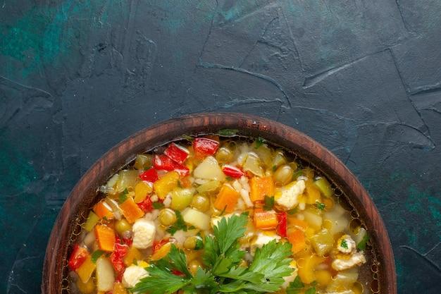 Bovenaanzicht heerlijke groentesoep met verschillende ingrediënten in bruine pot op donker bureau