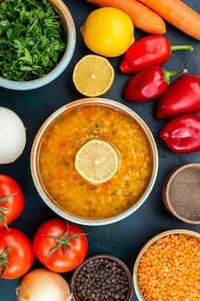 Bovenaanzicht heerlijke groentesoep met verse groenten greens en kruiden op donkerblauw bureau.