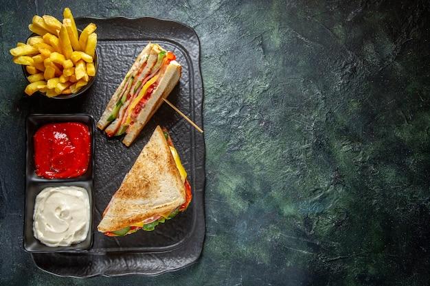 Bovenaanzicht heerlijke ham sandwiches met frietjes en kruiden donkere ondergrond