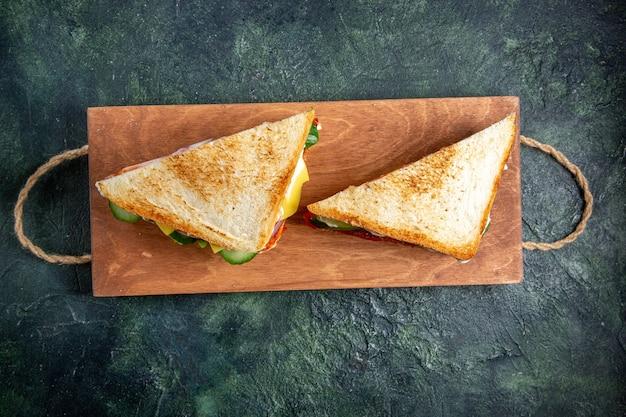 Bovenaanzicht heerlijke ham sandwiches op houten bord donkere ondergrond