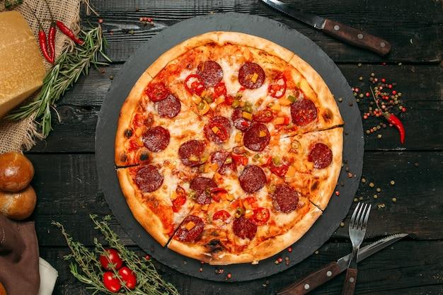 Bovenaanzicht heerlijke hartige pizza met horizontale worst en peper ,.