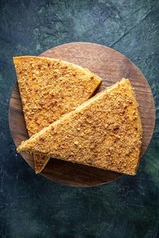 Bovenaanzicht heerlijke honing cake plak ervan op ronde houten bord