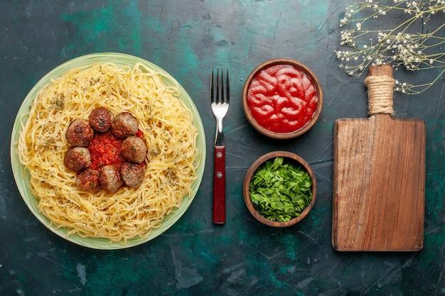 Bovenaanzicht heerlijke italiaanse pasta met gehaktballen en tomatensaus op de donkerblauwe achtergrond deeg pasta eten maaltijd schotel diner