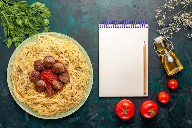 Bovenaanzicht heerlijke italiaanse pasta met gehaktballen en tomatensaus op de donkerblauwe achtergrond deeg pasta schotel vlees diner eten italië