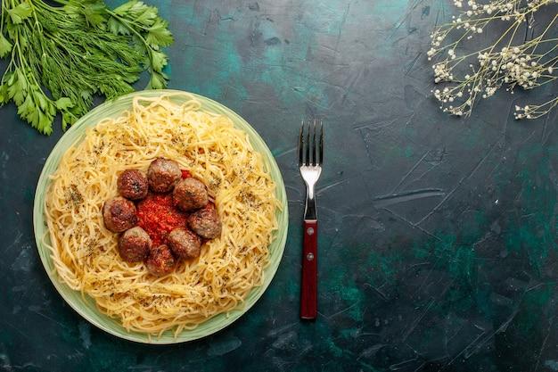 Bovenaanzicht heerlijke italiaanse pasta met gehaktballen en tomatensaus op donkerblauwe achtergrond deeg pasta gerecht diner eten italië