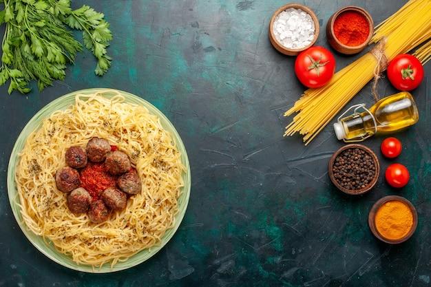 Bovenaanzicht heerlijke italiaanse pasta met gehaktballen en tomatensaus op het donkerblauwe bureau deeg pastaschotel vlees eten italië