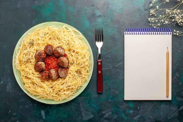 Bovenaanzicht heerlijke italiaanse pasta met gehaktballen en tomatensaus op het donkerblauwe oppervlak deeg pasta eten maaltijd schotel diner