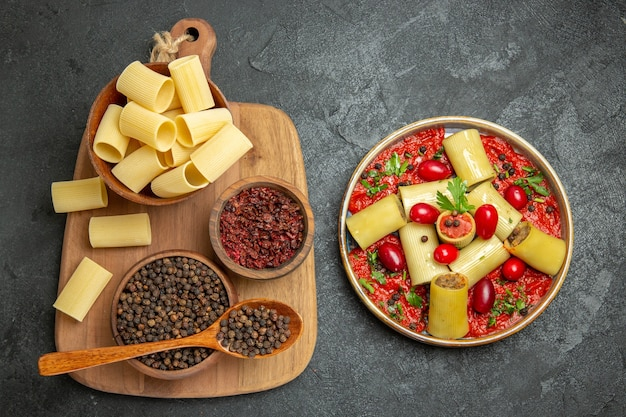 Bovenaanzicht heerlijke italiaanse pasta met tomatensaus en kruiden op grijs oppervlak pasta maaltijd eten vlees deeg