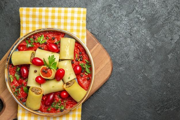 Bovenaanzicht heerlijke italiaanse pasta met vlees en tomatensaus op de grijze achtergrond maaltijd pasta deeg eten diner