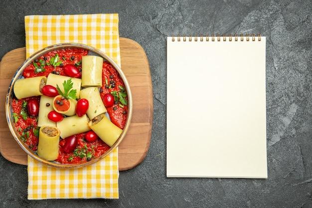 Bovenaanzicht heerlijke italiaanse pasta met vlees en tomatensaus op donkergrijze achtergrond maaltijd pasta deeg eten diner