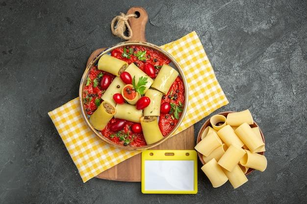 Bovenaanzicht heerlijke italiaanse pasta met vlees en tomatensaus op donkergrijze muur maaltijd pasta eten diner deeg