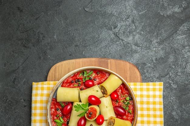 Bovenaanzicht heerlijke italiaanse pasta met vlees en tomatensaus op grijs bureau maaltijd pastadeeg eten diner