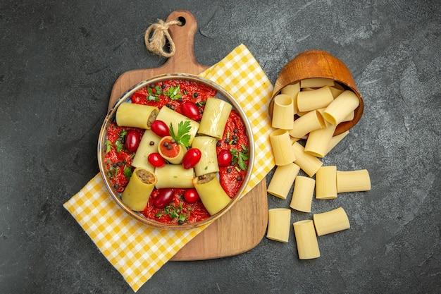 Bovenaanzicht heerlijke italiaanse pasta met vlees en tomatensaus op het donkergrijze oppervlak maaltijd pasta eten diner deeg