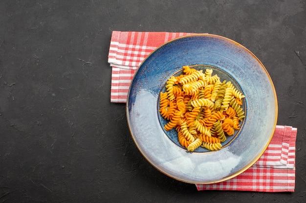 Bovenaanzicht heerlijke italiaanse pasta ongebruikelijke gekookte spiraal pasta op de donkere achtergrond pasta gerecht maaltijd koken diner