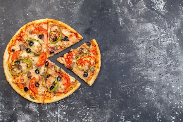 Bovenaanzicht heerlijke kaas pizza gesneden en geserveerd op een grijze ondergrond