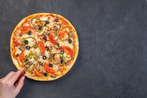 Bovenaanzicht heerlijke kaas pizza met olijven peper en tomaten op donkere ondergrond