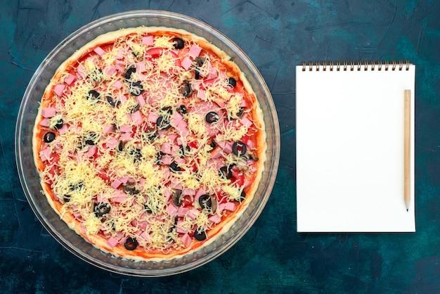Bovenaanzicht heerlijke kaas pizza met olijven tomatensaus worstjes in glazen pan met blocnote op lichtblauw bureau.