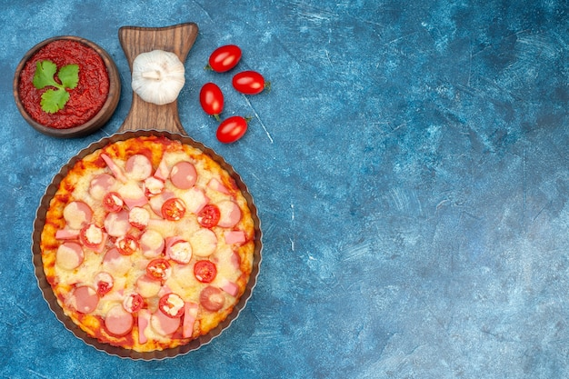 Bovenaanzicht heerlijke kaas pizza met worstjes en tomaten op blauwe achtergrond italiaans eten deeg cake fastfood foto kleur gratis plaats