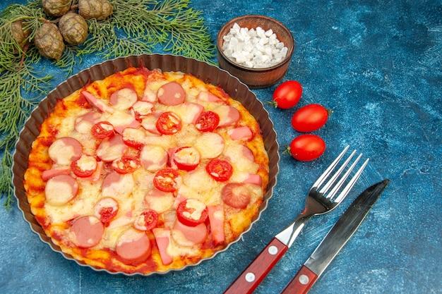 Bovenaanzicht heerlijke kaas pizza met worstjes en tomaten op blauwe achtergrond voedsel deeg cake kleur fastfood italiaans