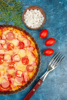 Bovenaanzicht heerlijke kaas pizza met worstjes en tomaten op de blauwe achtergrond voedsel deeg cake kleur foto fastfood italiaans