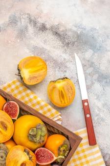 Bovenaanzicht heerlijke kaki en gesneden vijgen in houten kist gele keukenhanddoek een mes op naakte achtergrond