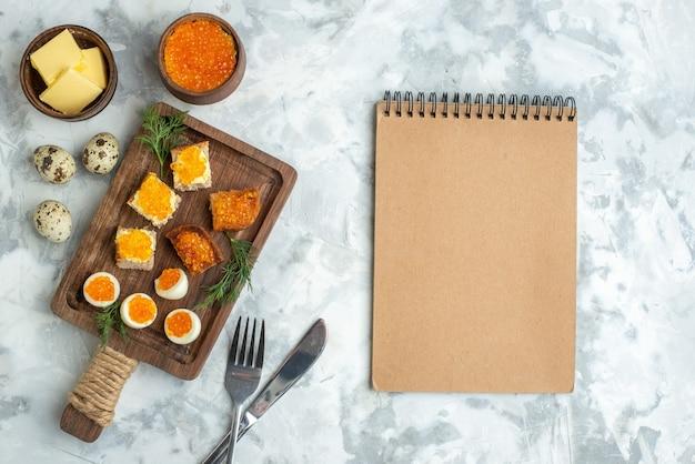Bovenaanzicht heerlijke kaviaar sandwiches met gekookte eieren op snijplank wit oppervlak ontbijt vis zeevruchten lunch eten horizontale maaltijd