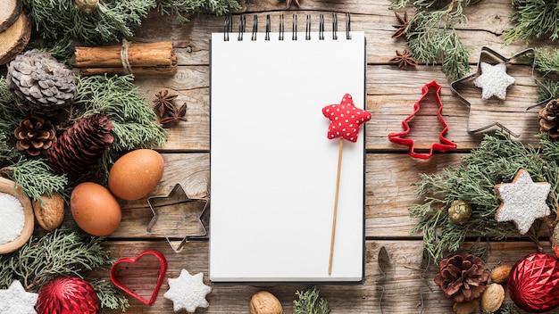 Bovenaanzicht heerlijke kerstlekkernijen met lege blocnote