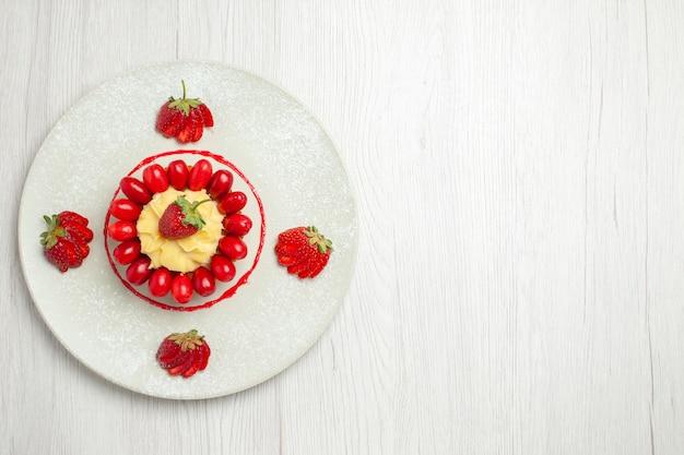 Bovenaanzicht heerlijke kleine cake met fruit op wit bureau
