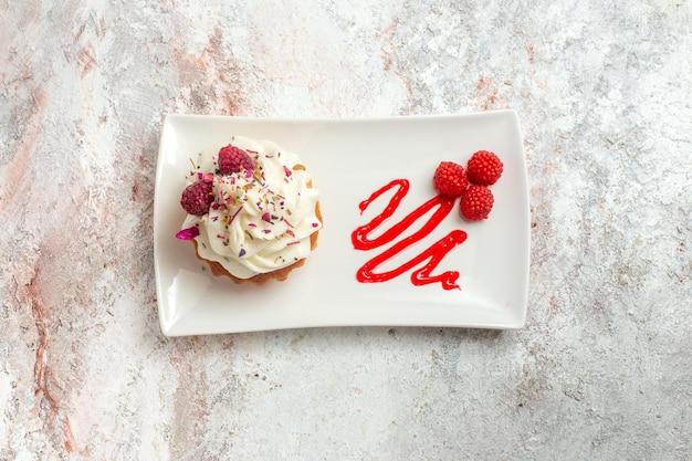 Bovenaanzicht heerlijke kleine cake met room en frambozen op witte achtergrond thee cake biscuit zoete room dessert
