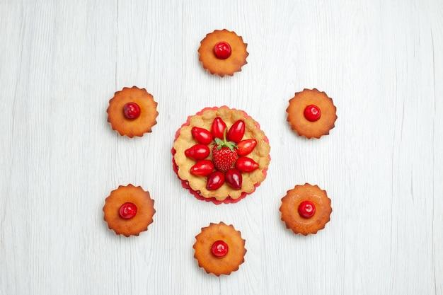 Bovenaanzicht heerlijke kleine cakes met fruit op wit bureau