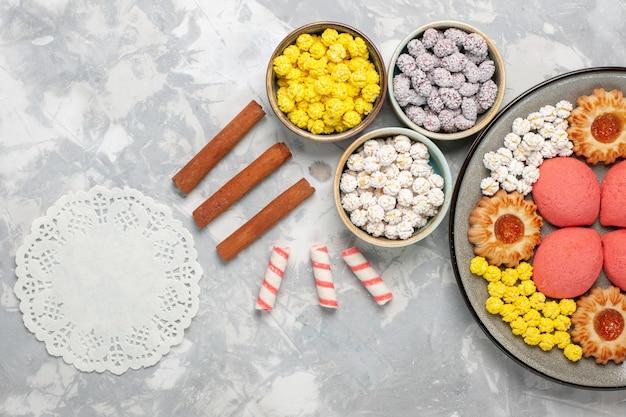 Bovenaanzicht heerlijke kleine cakes met koekjes en snoepjes op witte achtergrond suiker cake bakken biscuit taart thee cookie