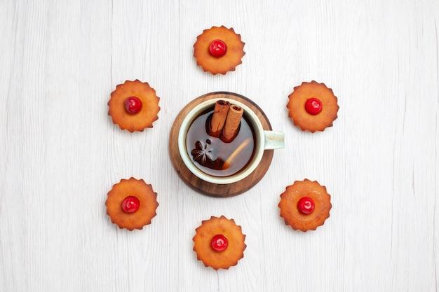 Bovenaanzicht heerlijke kleine cakes met kopje thee op wit bureau