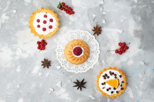 Bovenaanzicht heerlijke kleine cakes met room en rood fruit op het lichte bureau