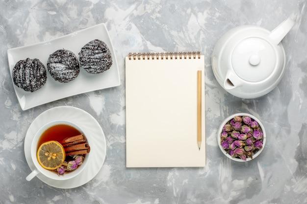 Bovenaanzicht heerlijke kleine cakes met suikerglazuur en kopje thee op de licht-witte achtergrond thee koekje cake bakken suiker zoete taart